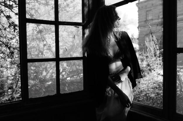 Jonge vrouw in lingerie en zwarte jas