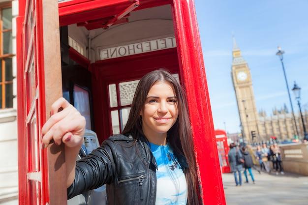 Jonge vrouw in londen met telefooncel en de big ben