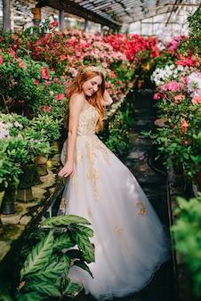 Jonge vrouw in luxueuze kleding die zich in bloementuin bevindt