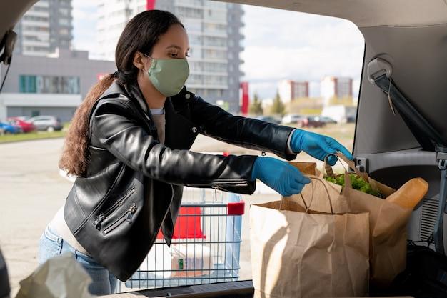 Jonge vrouw in masker en handschoenen papieren zakken ingebruikneming auto kofferbak na het winkelen in de supermarkt