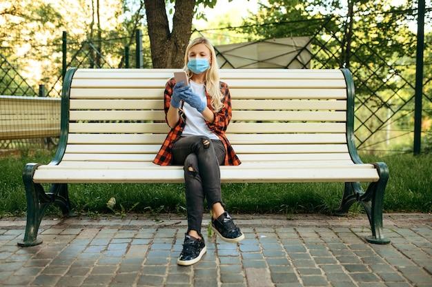 Jonge vrouw in masker zittend op een bankje in het park, quarantaine