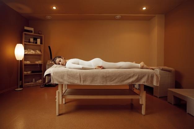 Jonge vrouw in massagepak ontspannen op tafel. massage en ontspanning, lichaams- en huidverzorging. vrouwelijke persoon liggend in de spa salon