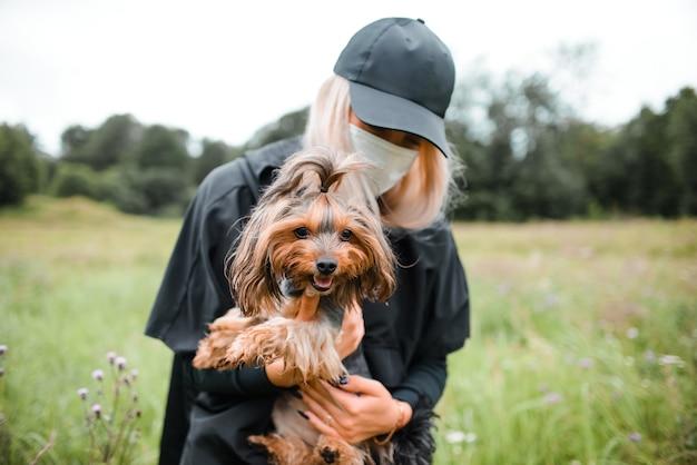 Jonge vrouw in medisch gezichtsmasker en de terriër van yorkshire. hond zit in handen van de eigenaar. nieuw normaal