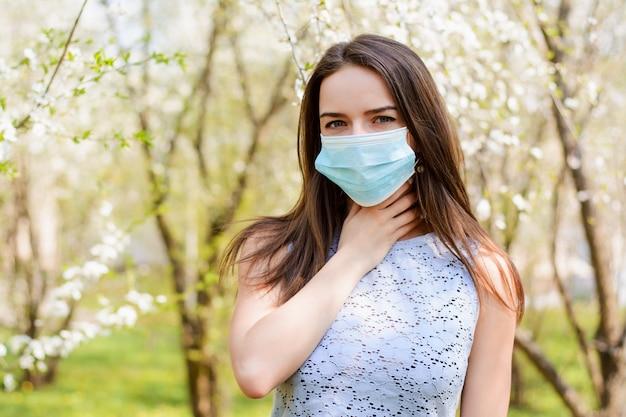 Jonge vrouw in medisch masker die keelpijn en allergie hebben die zich in openlucht tegen bloeiende bomen bevinden