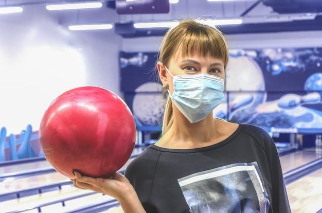 Jonge vrouw in medisch masker in de holdingskegelenbal van de bowlingclub van sporen en spelden. actieve vrijetijdsbesteding. sportieve gezinsactiviteiten. wazig getinte afbeelding met selectieve aandacht