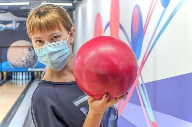 Jonge vrouw in medisch masker in de holdingskegelenbal van de bowlingclub