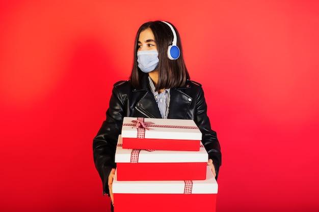 Jonge vrouw in medisch masker met hoofdtelefoons die giftdozen houden en weg geïsoleerd op rode muur kijken