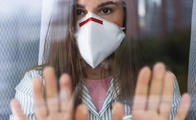 Jonge vrouw in medisch masker verblijf thuis isolatie voor zelfquarantaine.