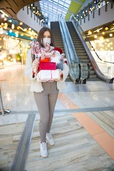 Jonge vrouw in medisch masker winkelen voor kerstcadeaus in winkelcentrum