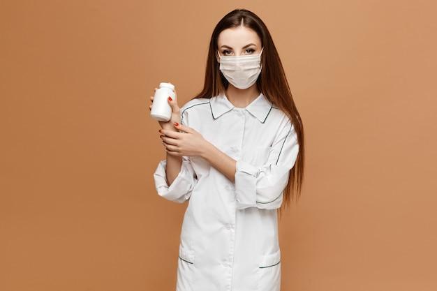 Jonge vrouw in medische kleding en beschermende masker poseren met potje pillen. de vrouwelijke arts houdt in hand pillen. virus en griep bescherming pillen concept.