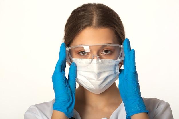 Jonge vrouw in medische kleding op een witte achtergrond