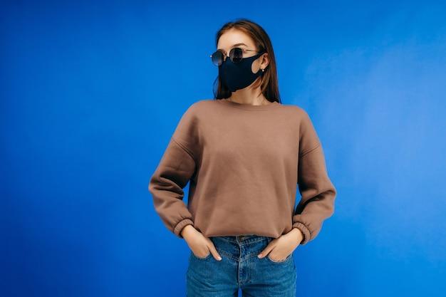 Jonge vrouw in medische masker, bril en hoodie poseren in studio op blauwe achtergrond
