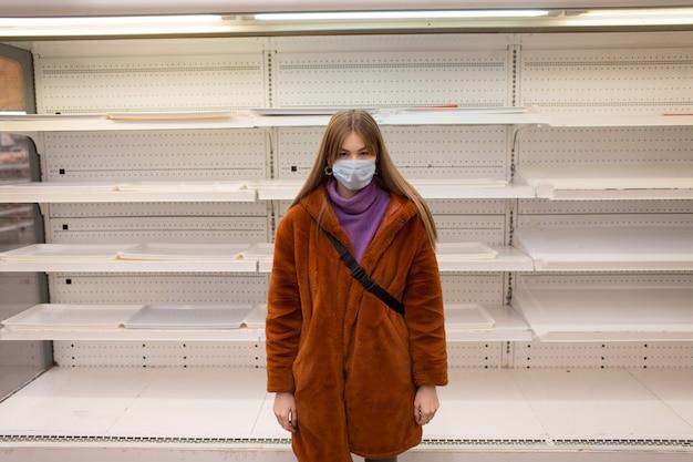 Jonge vrouw in medische masker en lege planken in de supermarkt