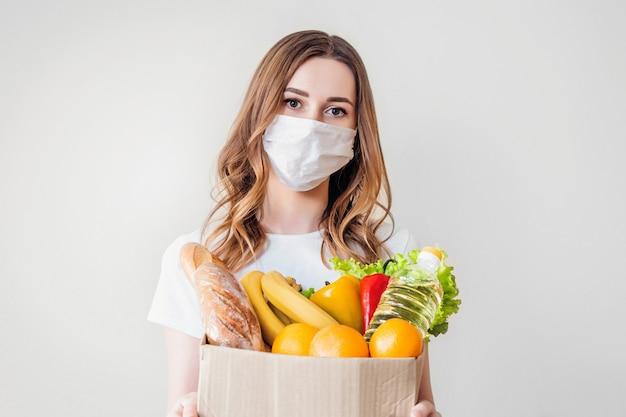 Jonge vrouw in medische masker houdt een kartonnen doos van papier met voedsel, groenten en fruit, stokbrood, sla over grijze achtergrond, levering aan huis, coronovirus, quarantaine, thuis blijven concept, kopie ruimte