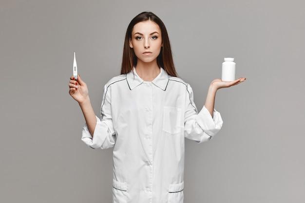 Jonge vrouw in medische uniform met een potje pillen in de ene hand en medische thermometer in een andere en poseren op de grijze achtergrond. concept van gezondheidszorg en geneeskunde