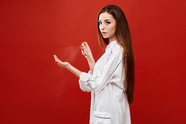 Jonge vrouw in medische uniform spuit een ontsmettingsmiddel op haar hand. vrouwelijke arts gebruik ontsmettingsmiddel spray voor het desinfecteren van haar handen. concept van gezondheidszorg en geneeskunde