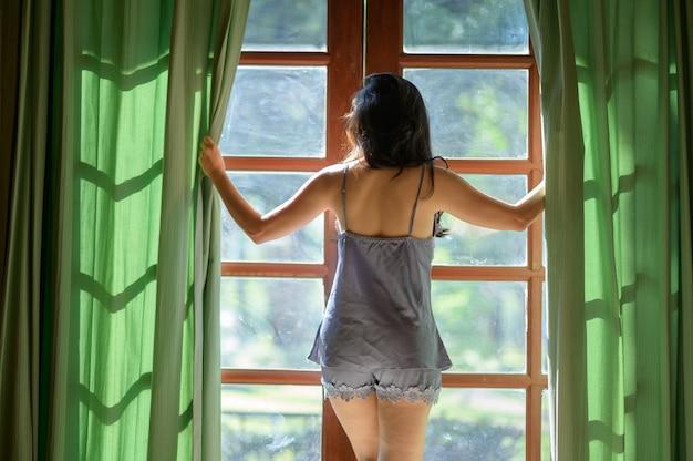 Jonge vrouw in modern appartement gordijnen openen na wakker worden