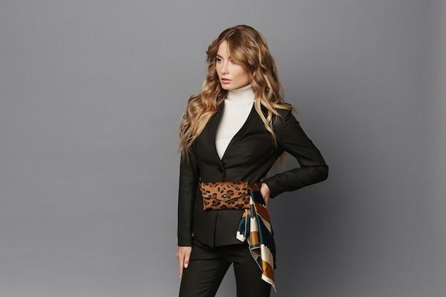 Jonge vrouw in modieus pak met luipaard riem tas poseren op een grijze achtergrond, geïsoleerd. mooi modelmeisje in formele kleding en met trendy heuptas met luipaardpatroon. lente mode