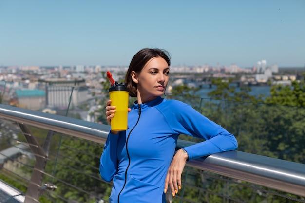 Jonge vrouw in montage sport slijtage op brug op warme zonnige ochtend met fles water shaker dorstig na training moe drinken