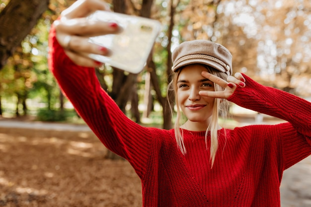 Jonge vrouw in mooie rode trui maakt selfie op het parkpad.