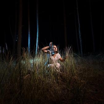 Jonge vrouw in nachtjapon zittend in het hoge bos 's nachts met lantaarn
