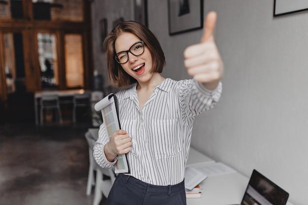 Jonge vrouw in office-stijl kleding en bril houdt tablet met documenten, knipoogt en verschijnt duim.