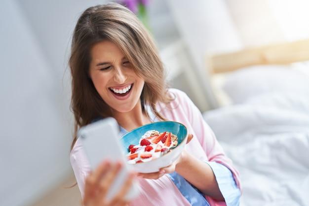 Jonge vrouw in ondergoed die granen eet
