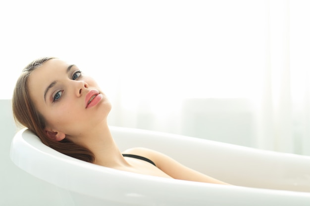 Jonge vrouw in ondergoed in badkuip