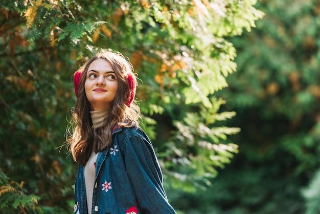 Jonge vrouw in oorbeschermers dichtbij groene takjes