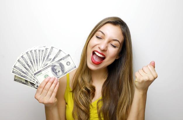 Jonge vrouw in opgewonden winnende pose, dollar biljetten te houden