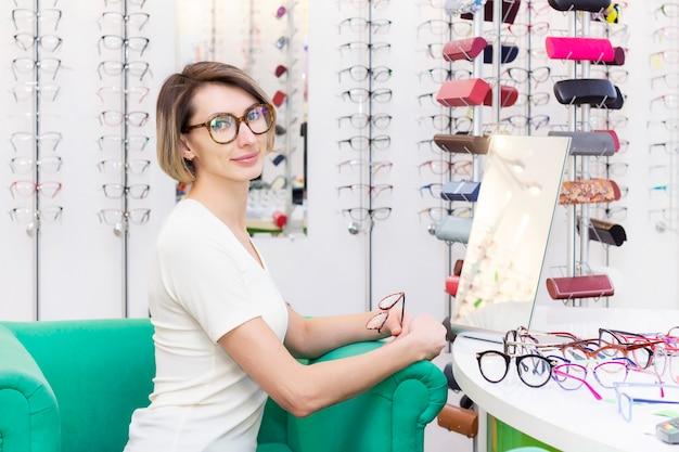 Jonge vrouw in optische winkel kiezen nieuwe bril met opticien. bril in de winkel van optica. een vrouw kiest een bril. emoties. oogheelkunde.
