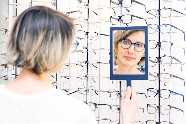 Jonge vrouw in optische winkel kiezen voor nieuwe bril met opticien