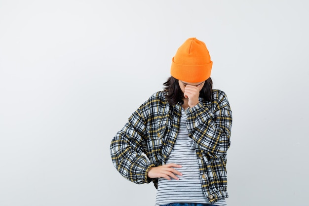 Jonge vrouw in oranje hoed en geruit hemd die met het hoofd op de hand leunt en van streek kijkt?
