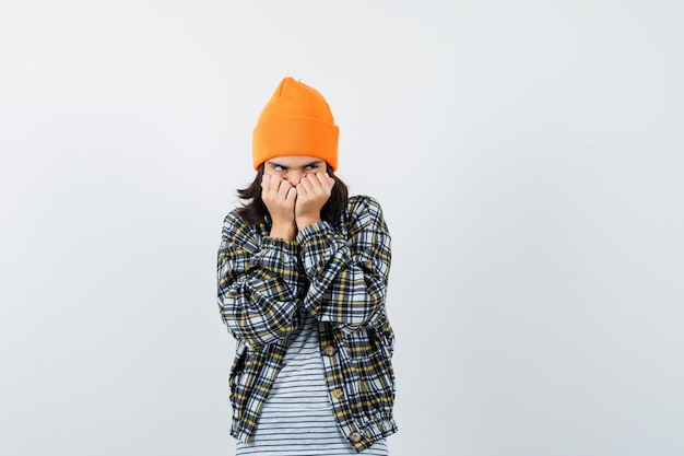 Jonge vrouw in oranje hoed geruit hemd met vuisten in de buurt van gezicht en kijkt bang