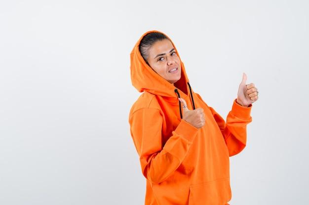 Jonge vrouw in oranje hoodie die met beide handen duimen laat zien en er mooi uitziet