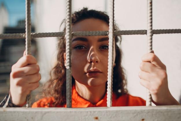 Jonge vrouw in oranje pak achter de tralies. wijfje in kleurrijk overallportret. wet en rechtvaardigheid concept.