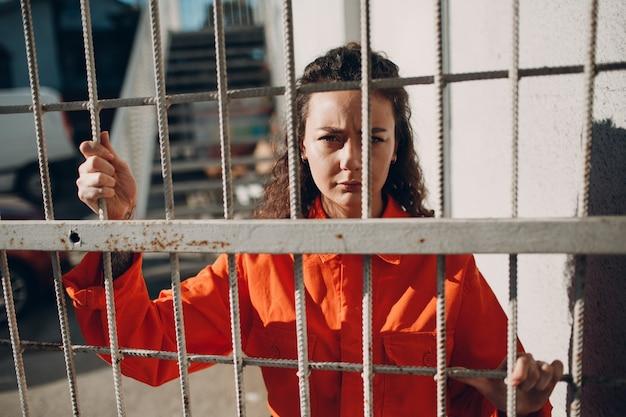 Jonge vrouw in oranje pak achter gevangenis bars vrouw in kleurrijke overall portret wet en rechtvaardigheid concept
