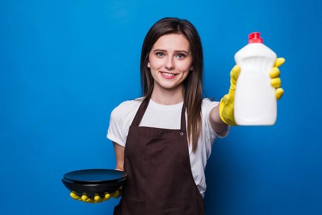 Jonge vrouw in oranje schort met gewassen plaat die geïsoleerde spons en afwasmiddel toont. beschermende handschoenen, afwasmiddel, spons - de beste hulp bij het afwassen