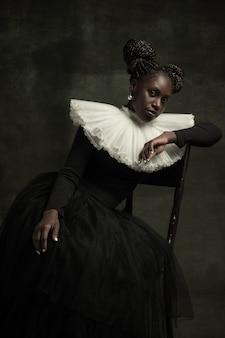Jonge vrouw in ouderwetse jurk zit op een stoel