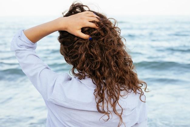 Jonge vrouw in overhemd die het overzees bekijken en haar haar houden
