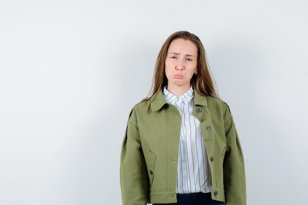 Jonge vrouw in overhemd, jas die lippen buigt, fronsend gezicht en neergeslagen kijkt, vooraanzicht.