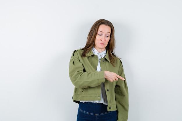 Jonge vrouw in overhemd, jas die naar beneden wijst en er optimistisch uitziet, vooraanzicht.