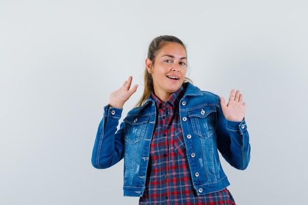 Jonge vrouw in overhemd, jasje zwaaiende handen om afscheid te nemen en op zoek blij, vooraanzicht.