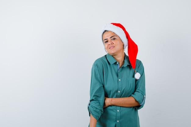 Jonge vrouw in overhemd, kerstmuts die de hand op de buik houdt en er zelfverzekerd uitziet, vooraanzicht.