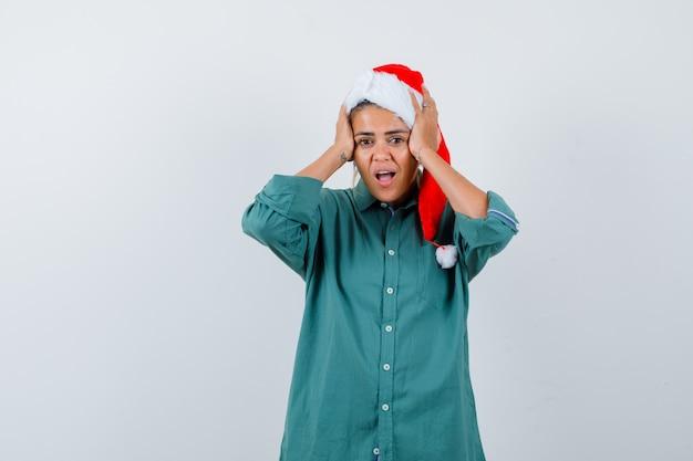Jonge vrouw in overhemd, kerstmuts die de handen op het hoofd houdt en er geschokt uitziet, vooraanzicht.