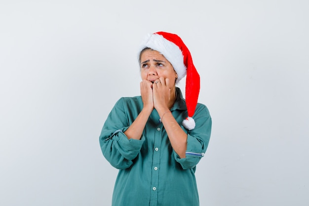 Jonge vrouw in overhemd, kerstmuts die handen op het gezicht houdt en er geschokt uitziet, vooraanzicht.