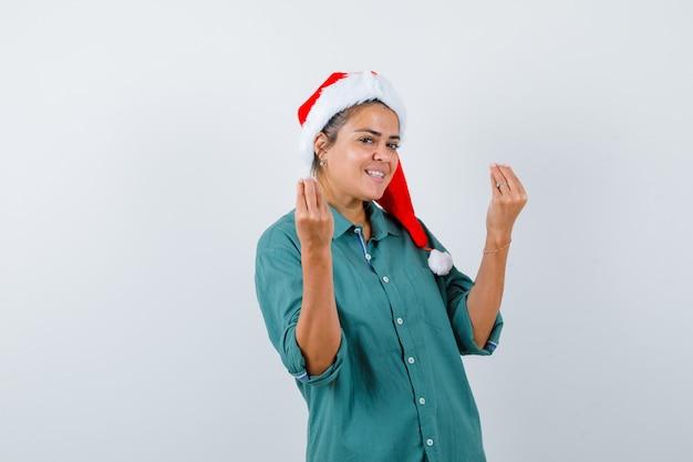Jonge vrouw in overhemd, kerstmuts die italiaans gebaar toont en er vrolijk uitziet, vooraanzicht.