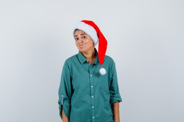 Jonge vrouw in overhemd, kerstmuts die lippen tuit en verbaasd kijkt, vooraanzicht.
