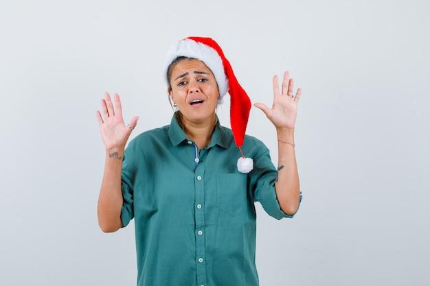 Jonge vrouw in overhemd, kerstmuts die overgavegebaar toont en hulpeloos kijkt, vooraanzicht.