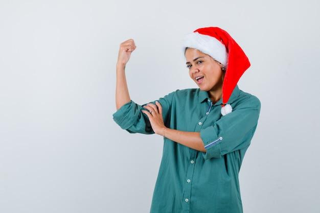 Jonge vrouw in overhemd, kerstmuts die spieren van de arm toont en er zelfverzekerd uitziet, vooraanzicht.